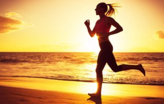 Woman running on the beach at sunset evening workout